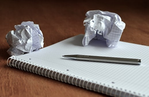 crumpled up paper, pen, and notepad