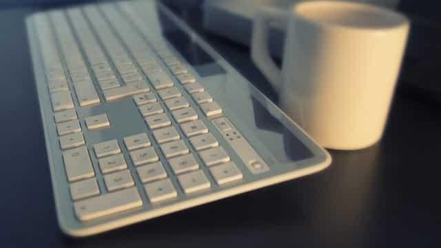 sleek keyboard next to coffee mug on shiny surface