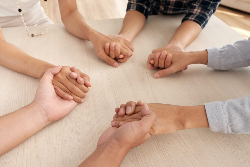 four unrecognizable people sitting around table holding each other s hands middle