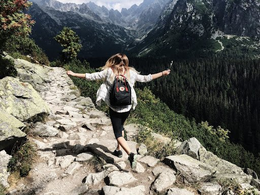 how to travel for free-young woman with backpack in the mountains