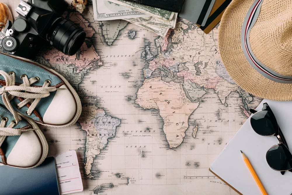 get paid to travel - flat map of the world with a pair of tennis shoes, a hat, and sunglasses laying on the edges