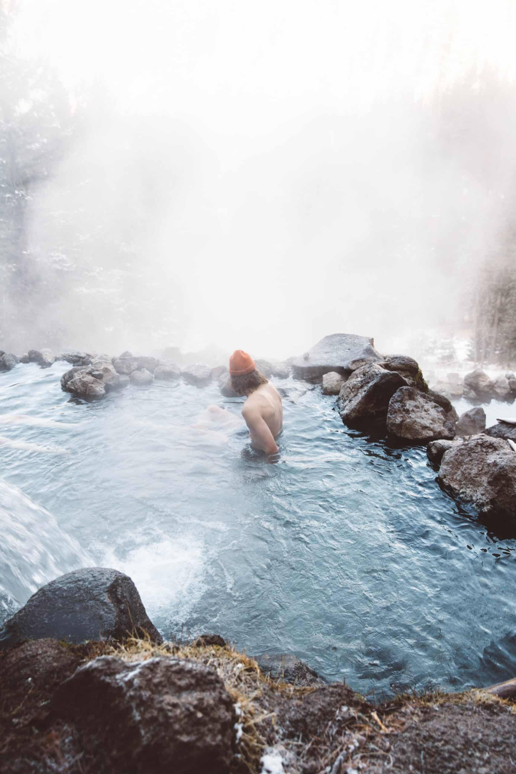 man in hot springs in the winter
